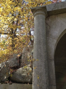Golden autumn leaves accent a column and stone wall.